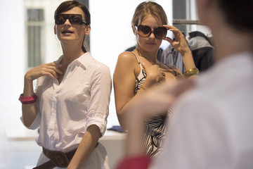 Women trying on sunglasses at a store.