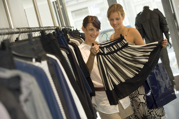 Women looking at a skirt in a boutique.