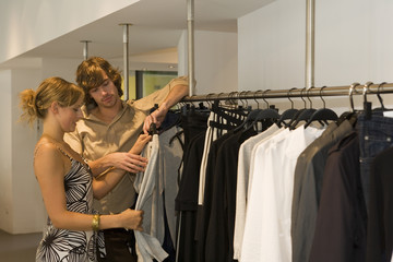 A couple looking at clothes in a boutique.