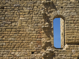 Stone wall of a castle with window, with blue sky