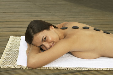 A young woman with therapeutic stones on her back.