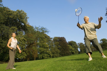 A senior couple playing badminton.