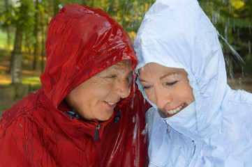 A senior couple wearing raincoats in the rain.