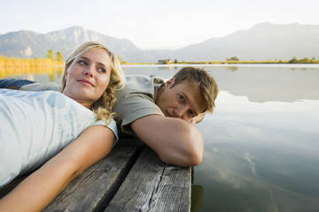 A couple lying down on a pier.