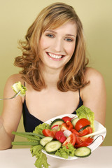 A woman sitting with a plate of salad.