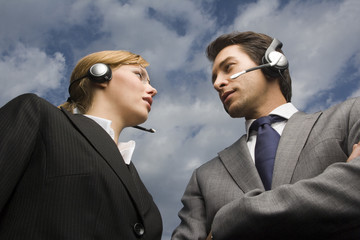 Two business people wearing headsets stand face to face.
