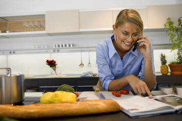 A woman talking on the phone in the kitchen.