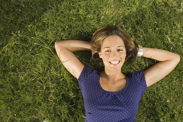 A teenage girl lying down on the grass.
