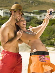 Couple taking their pictures on the beach.