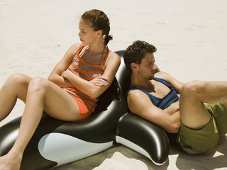 Couple sitting on an inflatable orca