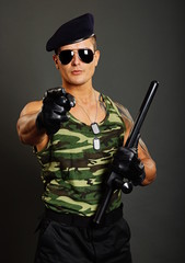 Young military man at sunglasses shows on you
