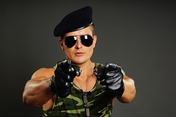 Military man at leather gloves shows on you