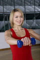 Woman doing weight training in gym.