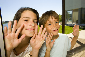 Boy and girl sticking their nose on the glass door