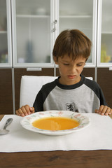 Boy sitting with a bowl of soup.