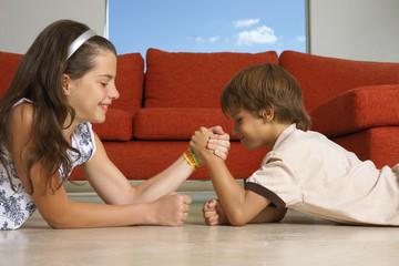 Siblings arm wrestling.
