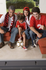 Family watching a sports match on TV