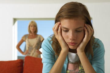 Girl upset, mother in the background.