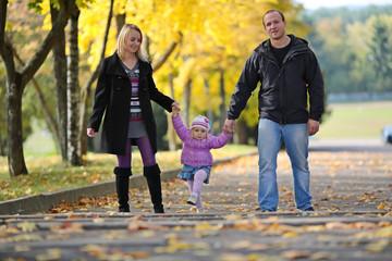 The happy family walks on autumn park