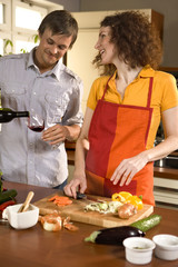 Woman cutting vegetables, man pouring wine.