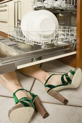 Woman lying under a dishwasher.