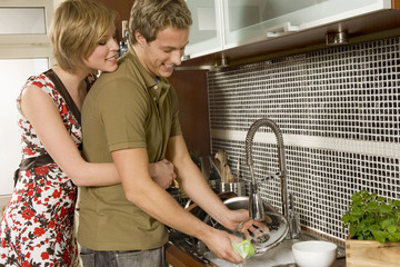 Woman hugging boyfriend washing dishes.