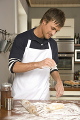 Man putting flour on dough.