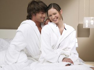 Couple in bathrobes sitting on bed.