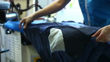 View of laundry worker ironing jacket