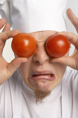 Chef covering eyes with tomatoes.
