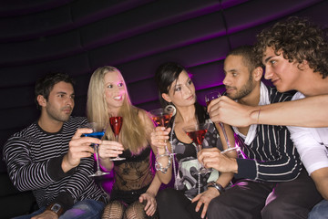 Five friends sitting in a nightclub and toasting martini glasses