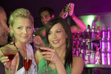 Two young women holding martini glasses at a bar counter