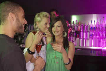 Two young women whispering in front of a young man at a bar counter