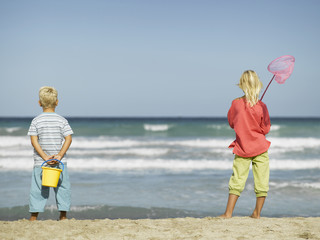 A girl and a boy standing on the beach