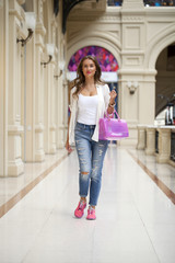 Beautiful young woman walks in the shop