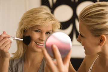 Close-up of a young woman applying blush with another young woman holding a mirror