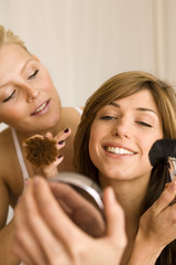 Close-up of a young woman looking at a mirror with another young woman looking at her