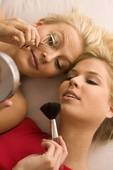 High angle view of a young woman curling eyelashes with another young woman holding a make-up brush