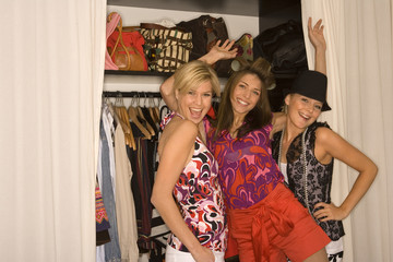 Portrait of three young women standing in front of a closet and smiling