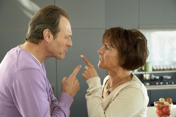 Mature couple pointing to each other