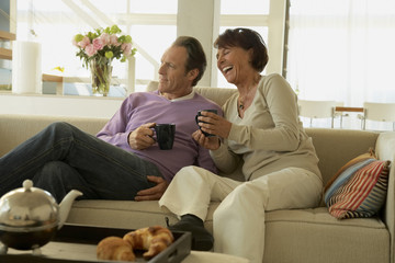Mature couple sitting on a couch and holding cups of coffee