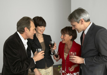 Four people holding wine glasses