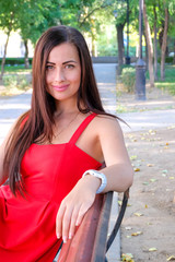 Beautiful fashionable girl sitting on park bench.