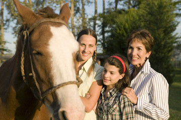 Three generation family with horse