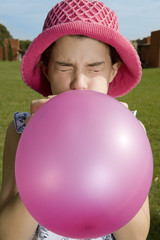 Girl blowing balloon up