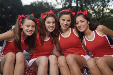 Portrait of four cheerleaders side by side and smiling