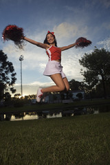 Low angle view of a cheerleader jumping and smiling