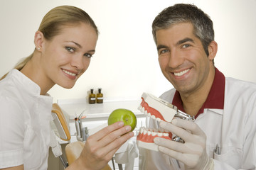 Portrait of a female assistant holding an apple in front of dentures in the hand of a male dentist