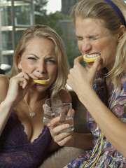 Close-up of two young women eating lemon slices and holding glasses