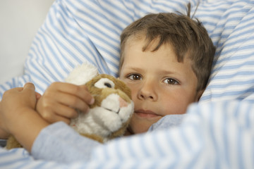Portrait of a boy playing with a stuffed toy